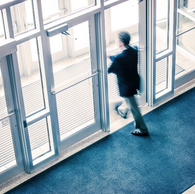 Man walking out of a clean corporate office building
