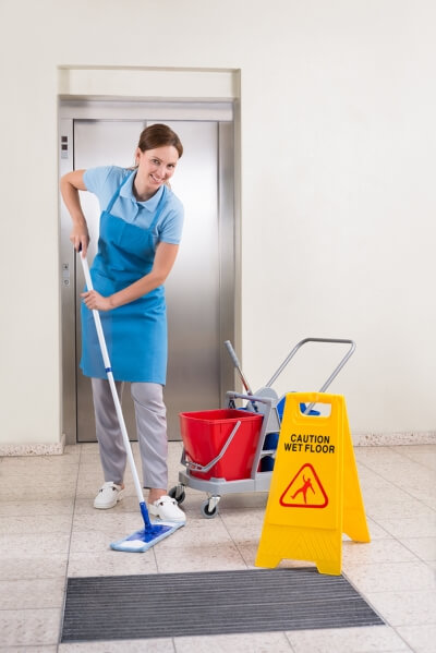 Female Janitor Cleaning a Hallway