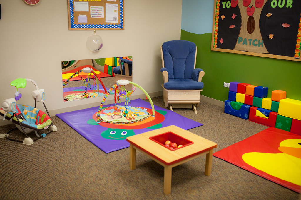 Clean daycare with colorful furniture.